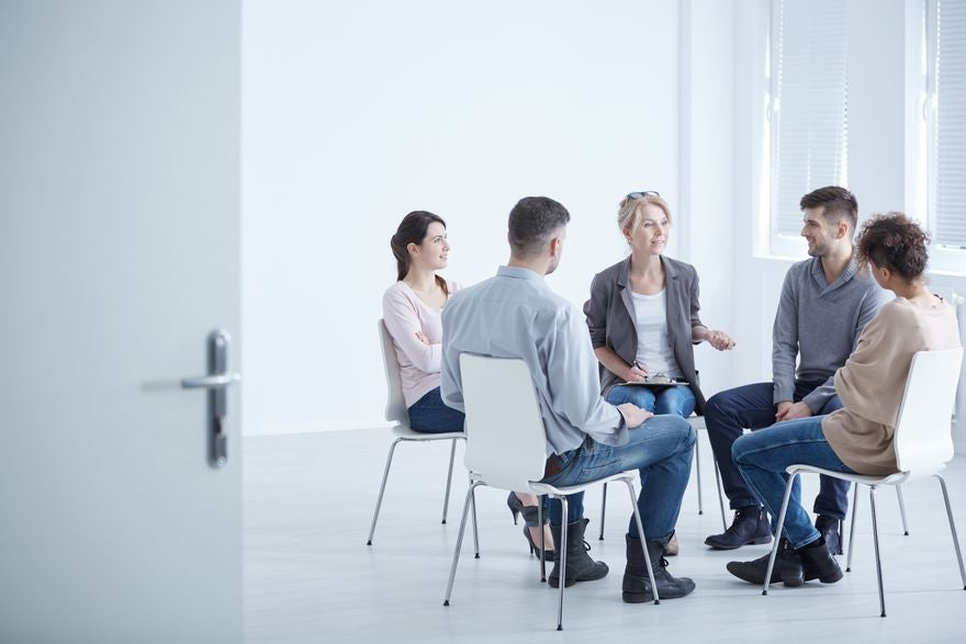 A group of people sit on chairs in a circle. A counsellor is talking and holding a clipboard, the others are listening.