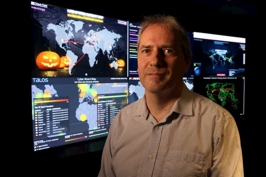 Associate Professor Paul Haskell-Dowland is smiling, standing in front of several large computer monitors with maps and graphs on them.