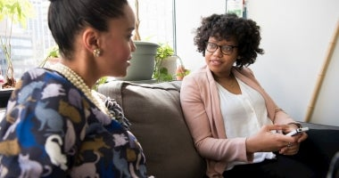 A counsellor and her client are sitting on a couch, the client is talking and the counsellor is listening intently.